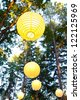 Yellow wedding decorations hang from the trees at a wedding ceremony and reception outdoors in Oregon. These yellow chinese lanterns or japanese lantersn are well lit. - stock photo