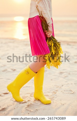 yellow wellies and yellow mimosa - stock photo