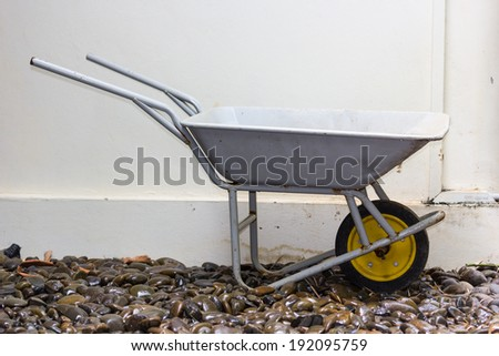 yellow wheelbarrow on wet river stones - stock photo