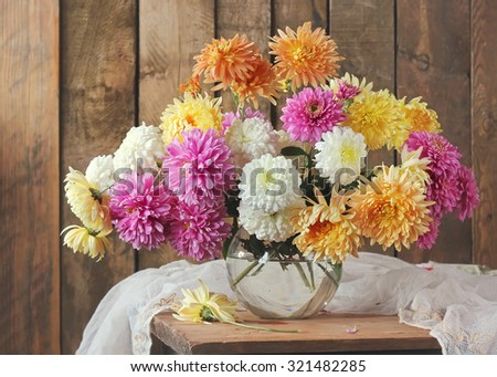 Yellow, white and pink chrysanthemums in a transparent vase against boards. Still life with a bouquet.