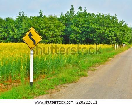 Yellow winding road sign along the natural splendor - stock photo