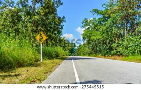 Yellow winding road sign at roadside in countryside of Thailand - stock photo