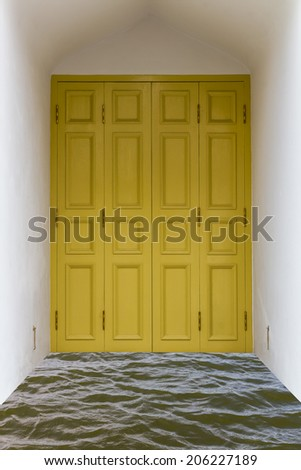 Yellow wooden door in white concrete box over the water. - stock photo