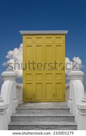 Yellow wooden door ,white columns, marble stairs ,Clouds, sky - stock photo