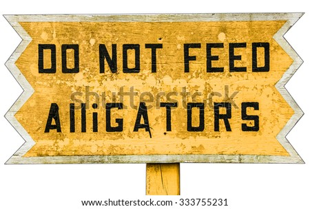 Yellow wooden warning sign with black text. Do not feed Alligators.. Vintage board in an alligator farm in Forida Everglades USA warning visitors not to feed animals, yellow background black type - stock photo