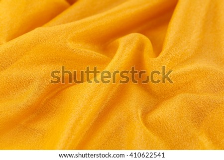 Yellow wrinkled fabric as a background. - stock photo