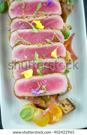 Yellowfin tuna with edible flowers and heirloom tomatoes - stock photo