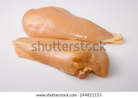 Yellowish chicken breasts isolated over white background. Yellow coloring come from chicken fed with corn grains - stock photo