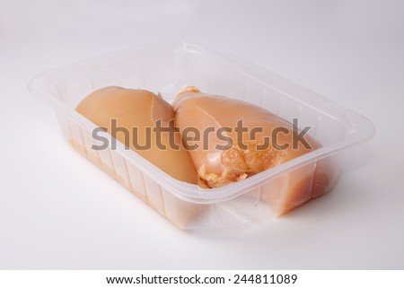 Yellowish chicken breasts isolated over white background. Yellow coloring is because chicken fed with corn grains - stock photo
