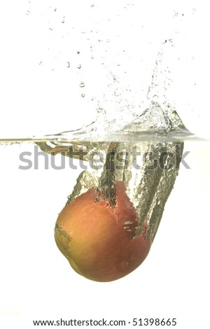 Yellowish red apple splashing in water with bubbles in white background