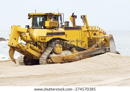 yellows excavators on the city  beach working sand moving in Corunna Spain