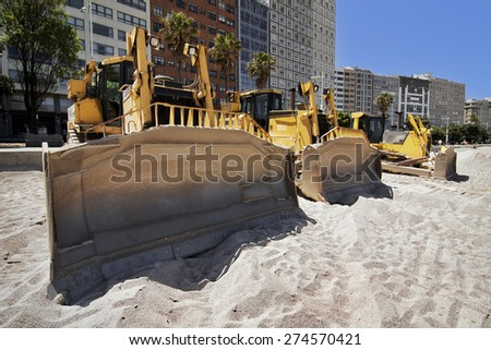 yellows excavators on the city  beach working sand moving in Corunna Spain - stock photo