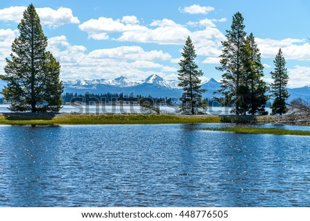 Yellowstone Lake - A spring view of Yellowstone Lake with snow-capped mountain range in the background, Yellowstone National Park, Wyoming, USA. - stock photo