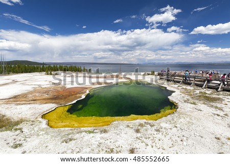 Yellowstone National Park, Wyoming, USA - July 26, 2016: Tourists walking along the shore of Yellowstone lake at West Thumb Geyser Basin