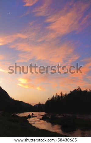 Yellowstone river early in the morning as the sunrises coloring the clouds and with a new moon in, Yellowstone National Park - stock photo