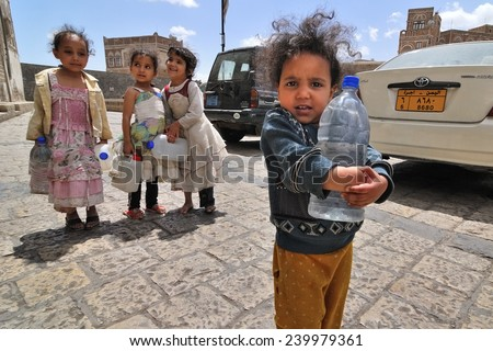 YEMEN, SANA - MAR 6, 2010: Unidentified girls with empty water-pots going in search of drinking water in Sana, Yemen. Girls grow up in the poorest country with little opportunity for education - stock photo