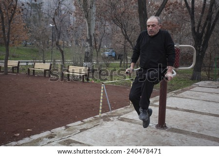 YEREVAN, ARMENIA - 29 DECEMBER, 2014: An undefined old man outdoor workout trainings