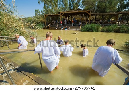 YERICHO, ISRAEL - OCT 15, 2014: Religious christians with white clothes going into the water of the Jordan river at baptismal site Qasr el Yahud near Yericho - stock photo