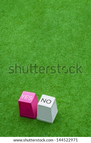 Yes and No buttons from keyboard on fake grass - stock photo