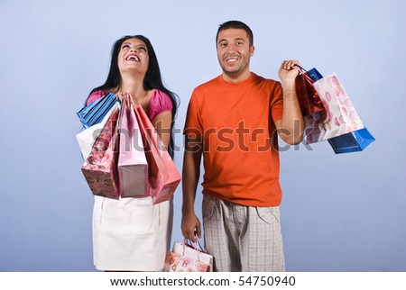 Yes!I did it!Bought what i wanted!Shopaholic woman it is extremely happy and laughing and the guy smiling and looking  doubt and surprised - stock photo