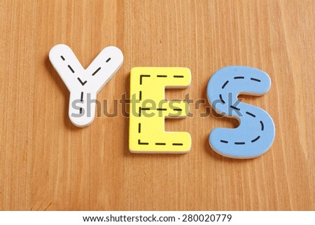 YES, spell by woody puzzle letters with woody background - stock photo
