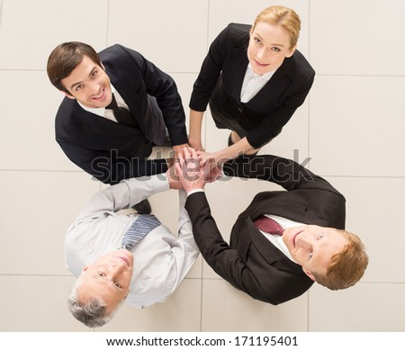 Yes, we are the best! Top view of four cheerful people in formalwear clasping their hands together and looking at camera - stock photo