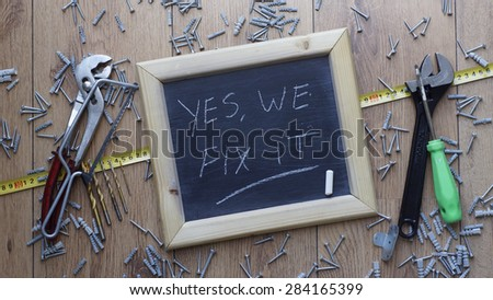 Yes, we can fix it written on a chalkboard next to tools, screws and dowels - stock photo