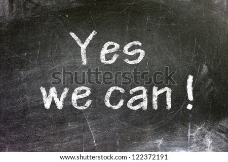 yes we can written on blackboard - stock photo