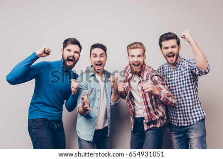 Yes! Winners! Four cheerful young men are standing and gesturing for the victory on pure background in casual outfit and jeans. They are fans of sports games as football, basketball, hockey, baseball