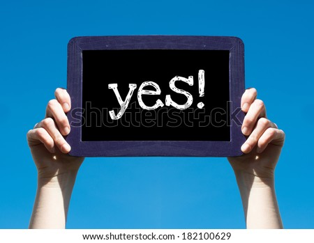 Yes ! Woman holding blackboard over blue background with text Yes ! - stock photo
