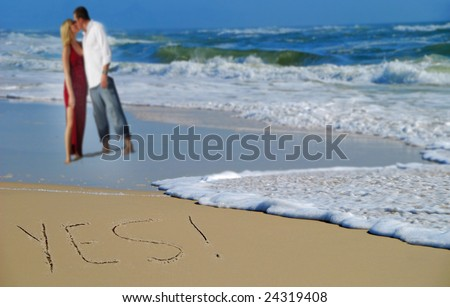 Yes written in sand with couple and waves in background - stock photo