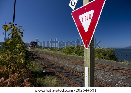 Yield sign at a railroad crossing - stock photo