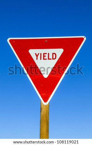 yield Sign at the highway with blue sky - stock photo