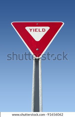 Yield sign on blue sky, isolated with clipping path - stock photo