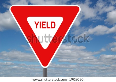 Yield sign with clouds in the background - stock photo