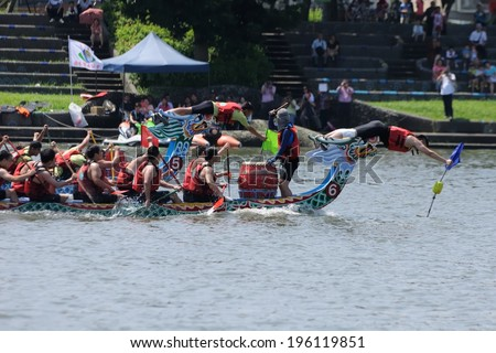 YILAN TAIWAN - JUNE 1: green team and blue team's flag fetcher snatched the flag almost at same time. The Dragon Boat Festival on the Dongshan River on June 1, 2014 in Yilan - stock photo