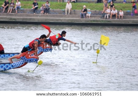 YILAN TAIWAN - JUNE 24: red team's flag fetcher first snatched the flag at the end point.   The Dragon Boat Festival  on the Dongshan River on June 24, 2012 in Yilan - stock photo