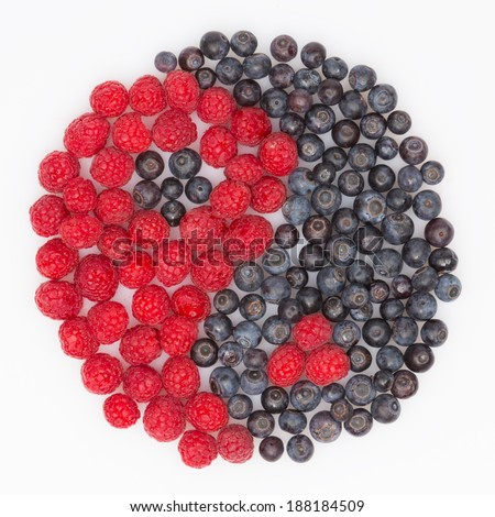yin and yang of berries of red raspberries and blueberries on white background