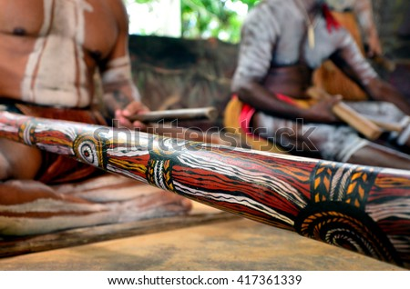 Yirrganydji Aboriginal men play Aboriginal music on didgeridoo and wooden instrument during Aboriginal culture show in Queensland, Australia. - stock photo