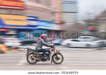 YIWU-CHINA-JAN. 26, 2016. Man on a motorbike. The government want to ban out gas scooters and motorbikes that are popular in Chinese cities because they are loud and dirty in terms of air pollution. - stock photo