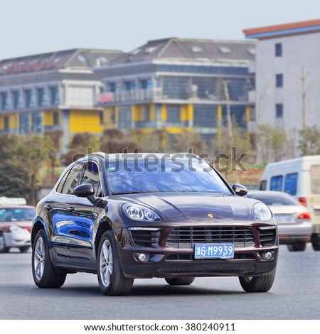 YIWU-CHINA-JAN. 25, 2016. Purple Porsche Macan. The Macan is 42% cheaper than the Cayenne, pushes growth rates to 20 percent and lifting overall Porsche sales to almost 60,000, beating the U.S. sales. - stock photo