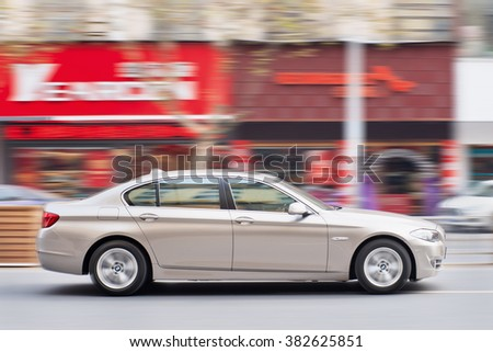 YIWU-CHINA-JANUARY 19, 2016. BMW 5 series L on the road. BMW sales will be hit in 2016 by cut-throat competition, slowing Chinese economy and government crackdown on graft and conspicuous consumption. - stock photo