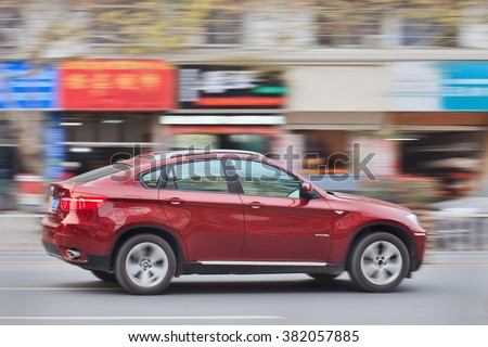 YIWU-CHINA-JANUARY 15, 2016. BMW X6 3.5i on the road. BMW sales will be hit in 2016 by cut-throat competition, slowing Chinese economy and government crackdown on graft and conspicuous consumption. - stock photo