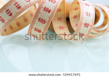 Yo-yo effect in diet concept. Centimeter tape measure. Reflective glass background. Copy space on the bottom.