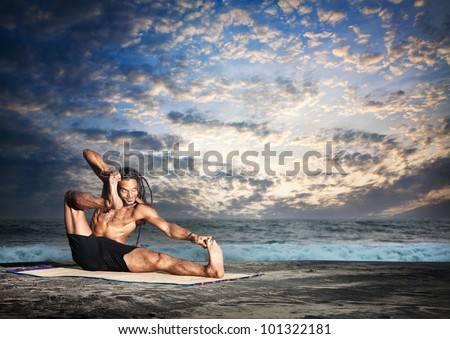 Yoga akarna dhanurasana archer pose by fit man with dreadlocks on the beach in the evening at ocean background - stock photo