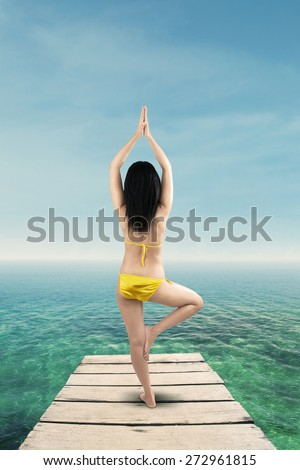 Yoga and fitness, sexy woman wearing bikini and meditating on the jetty - stock photo