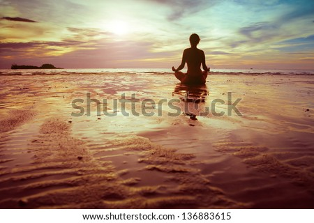 yoga and fitness, silhouette of woman meditating on the beach - stock photo