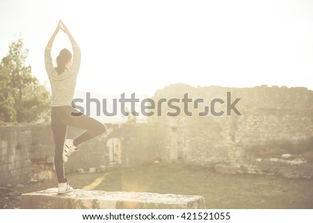 Yoga and meditation concept.Woman meditating in sitting yoga position outdoors.Woman alone practicing mindfulness meditation to clear her mind.Zen,meditation,peace concept - stock photo