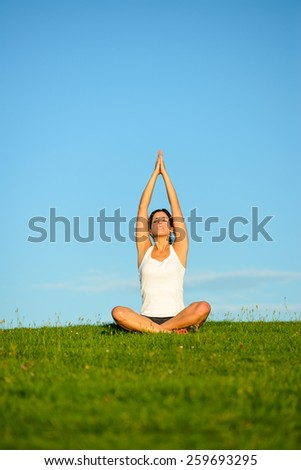 Yoga and relax. Young woman doing relaxing and breathing exercise outdoor. healthy lifestyle, wellness and tranquility concept at green grass field towards blue clear sky. - stock photo