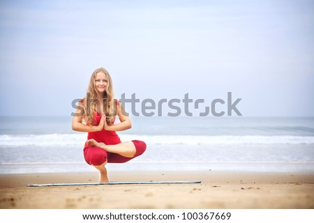 Yoga Ardha Baddha Padma Padangusthasana balancing on toes by young woman with long hair in red cloth on the beach at ocean background - stock photo